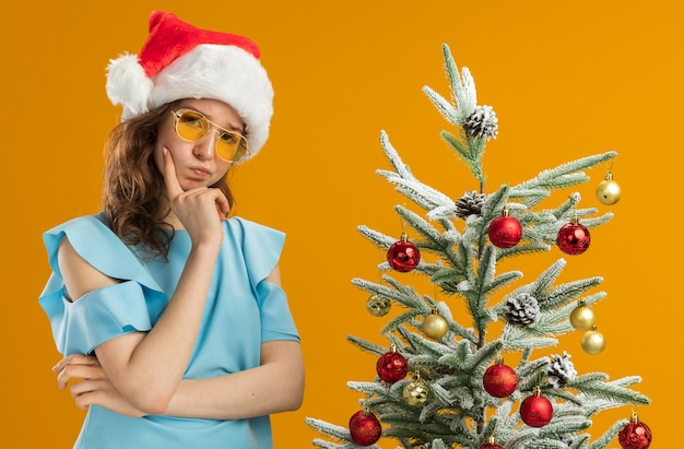 Junge frau in blauem oberteil und weihnachtsmütze mit gelber brille mit der hand am kinn, die denkt, neben einem weihnachtsbaum über orangefarbener wand zu stehen