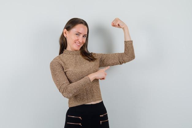 Junge frau in bluse, rock zeigt auf ihren armmuskel und schaut glücklich, vorderansicht.