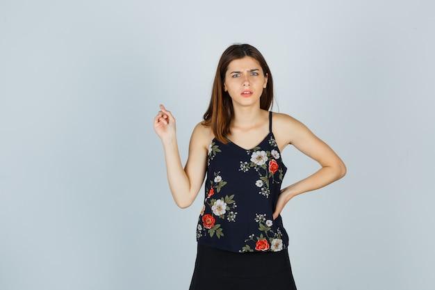 Junge frau in bluse, rock zeigt nach hinten, während sie die stirn runzelt und verwirrt aussieht, vorderansicht.