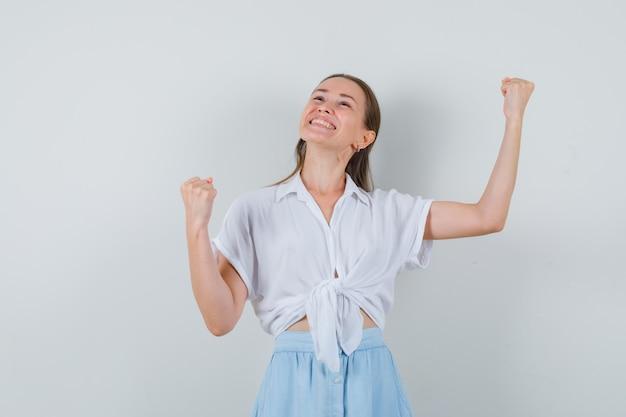 Junge frau in bluse und rock zeigt siegergeste und sieht glücklich aus