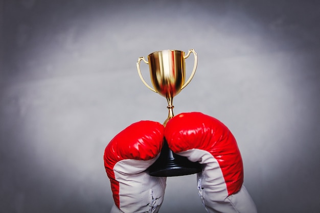 Junge frau in boxhandschuhen mit goldener tasse