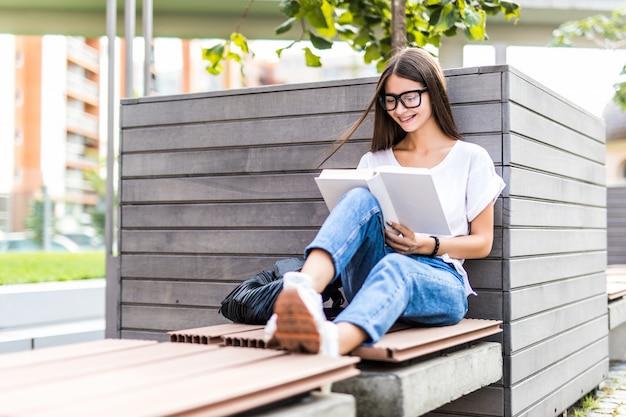 Junge frau in brillen, die auf bank sitzen und buch lesen