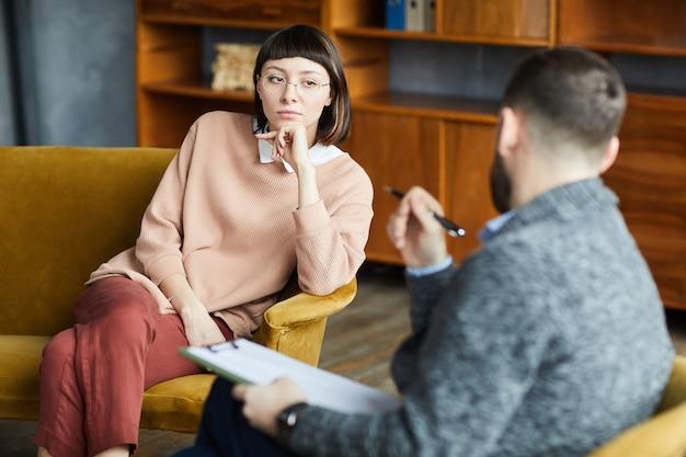 Junge frau in brillen, die auf sofa sitzen und mit dem mann während ihres besuchs der psychologietherapie sprechen