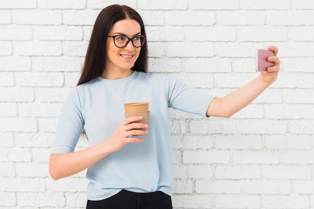 Junge frau in den gläsern, die selfie mit kaffeetasse nehmen