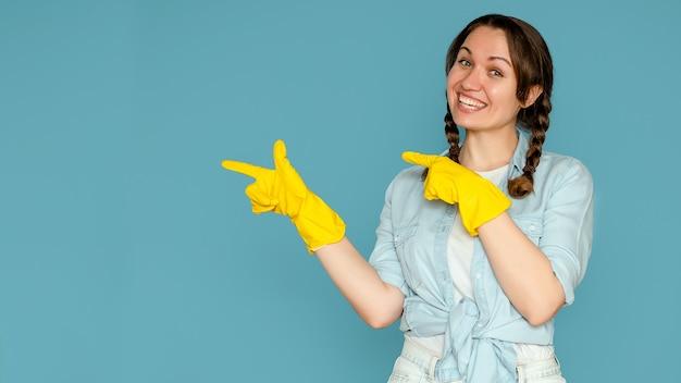 Junge frau in den handschuhen für die reinigung auf einem isolierten blauen hintergrund