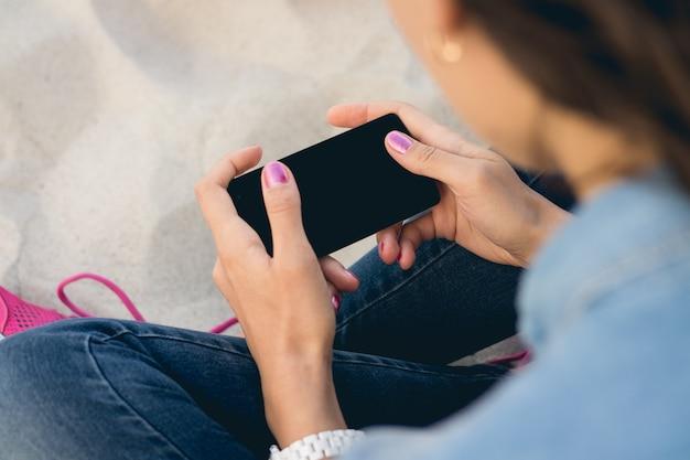 Junge frau in den jeans, die auf dem sand sitzen und einen handy mit einem touch screen mit zwei händen verwenden