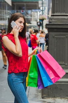 Junge frau in den jeans, die mit einkaufstaschen telefonieren