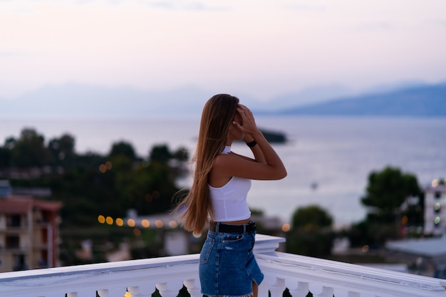 Junge frau in den jeansshorts, die auf dem balkon stehen und den meerblick und den schönen sonnenuntergang betrachten. urlaub auf tropischer insel. luxuskonzept.