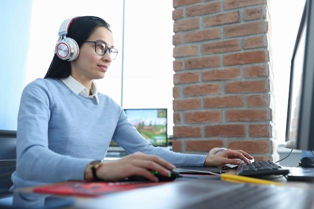 Junge frau in den kopfhörern, die am computer arbeiten. freiberufliches konzept