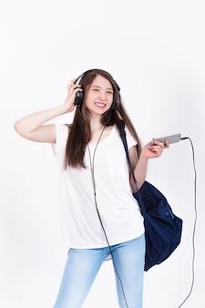 Junge frau in den kopfhörern, die lieder auf einer weißen wand singen