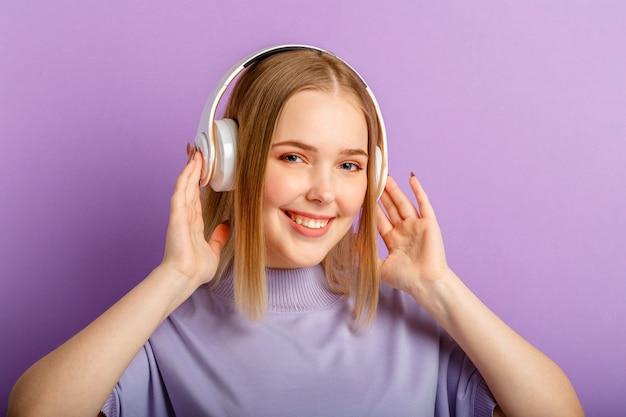 Junge frau in den kopfhörern mit blondem frisurporträt des schönen lächelns. teenager-mädchen genießen es, song-musik zu hören, die sich in kopfhörern bewegt, die über lila farbhintergrund isoliert sind