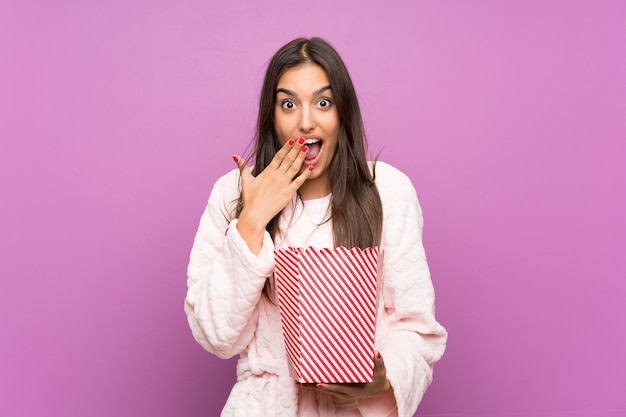 Junge frau in den pyjamas und im hausmantel über lokalisierter purpurroter wand, die popcorn hält