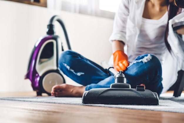 Junge frau in den schutzhandschuhen, die haus mit staubsauger im wohnzimmer zu hause reinigen