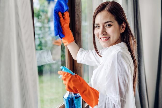 Junge frau in den schutzhandschuhen unter verwendung eines sprays und eines lappens beim reinigen des fensters im wohnzimmer zu hause. hausarbeit und hauptreinigungskonzept
