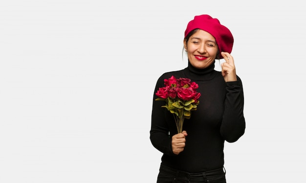 Junge frau in den valentinsgrußtagesüberfahrtfingern für das glück haben