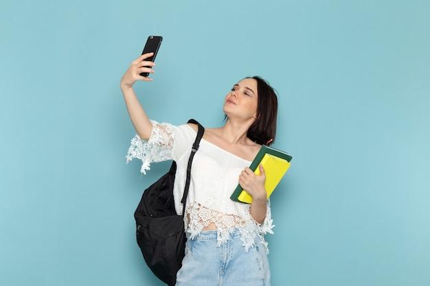 Junge frau in den weißen jeans des weißen hemdes und der schwarzen tasche, die hefte hält, die ein selfie auf blau nehmen