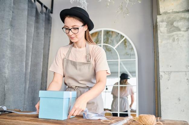 Junge frau in der arbeitskleidung und im hut, die durch holztisch stehen und blaue geschenkbox mit seidenband binden