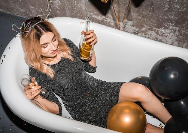 Junge frau in der badewanne zu hause betrunken