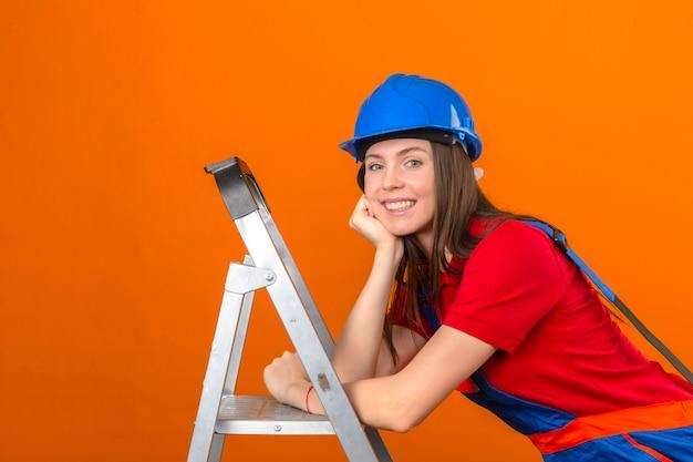 Junge frau in der bauuniform und im blauen sicherheitshelm auf leiter mit lächeln auf gesicht auf lokalisiertem orange hintergrund