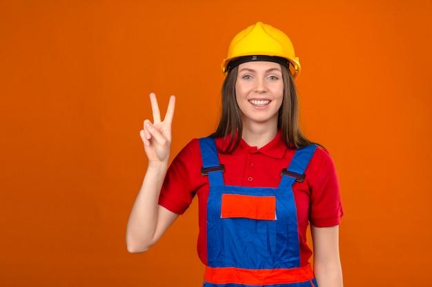 Junge frau in der bauuniform und im gelben sicherheitshelm, der das lächelnde siegeszeichen nummer zwei zeigt, das auf orange hintergrund steht