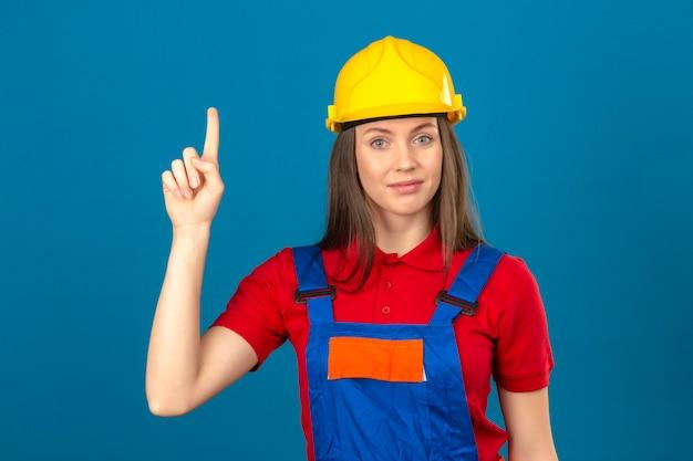 Junge frau in der bauuniform und im gelben sicherheitshelm, der neue idee zeigt, finger oben auf blauem hintergrund stehend