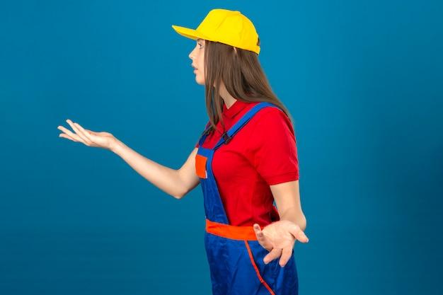 Junge frau in der bauuniform und im gelben sicherheitshelm gestikulierend mit achselzucken stehend auf blauem hintergrund