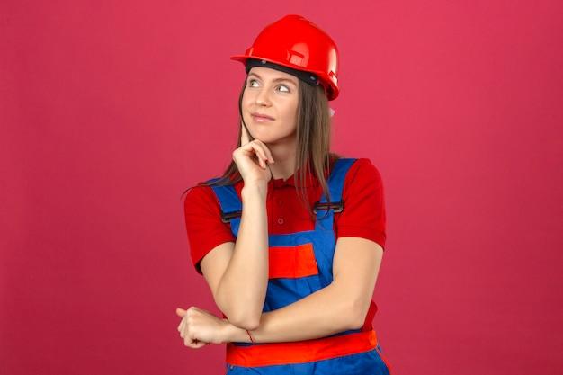 Junge frau in der bauuniform und im roten sicherheitshelm lächelnd denkend eine neue idee, die auf dunkelrosa hintergrund steht