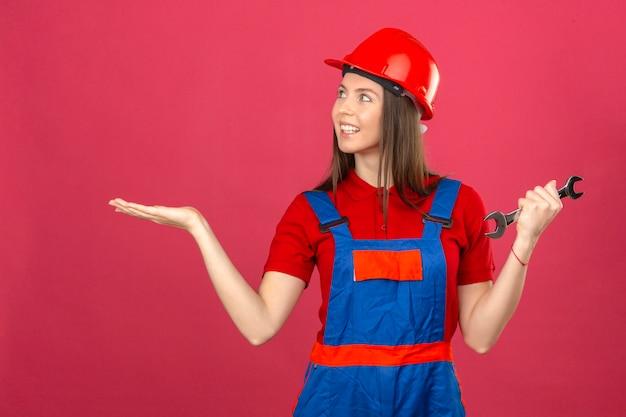Junge frau in der bauuniform und im roten sicherheitshelm lächelnd, die fröhlich präsentiert und mit handfläche zeigt und schraubenschlüssel auf dunkelrosa hintergrund hält