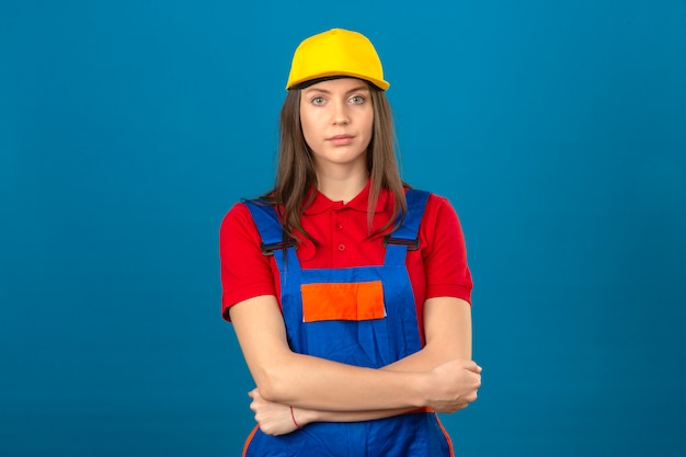 Junge frau in der bauuniform und in der gelben kappe, die mit verschränkten armen steht, die kamera mit ernstem gesicht auf blauem hintergrund betrachten