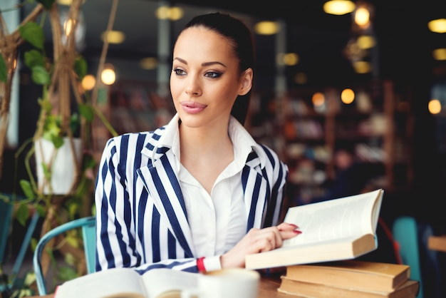 Junge frau in der bibliothek. einen kaffee trinken und ein buch lesen. entspannung und bildung, buch und kaffee genießen.
