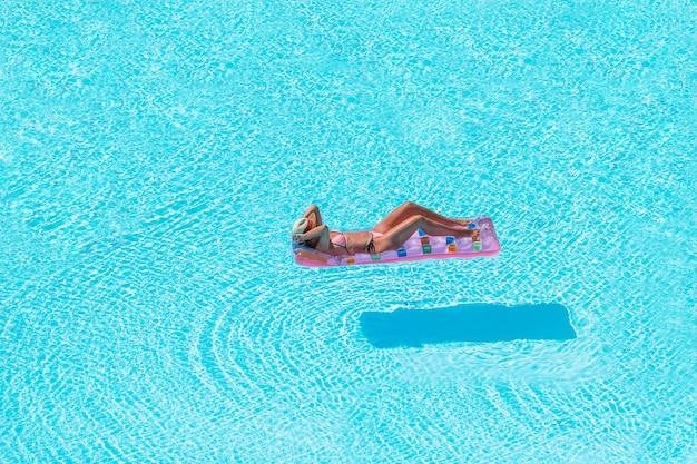 Junge frau in der bikiniluftmatratze im großen swimmingpool