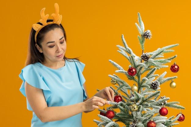 Junge frau in der blauen spitze, die lustige felge mit hirschhörnern trägt, die weihnachtsbaum glücklich und positiv stehend über orange hintergrund verzieren
