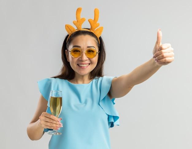Junge frau in der blauen spitze, die lustige felge mit hirschhörnern und gelben gläsern hält, die glas champagner halten, das glückliches und fröhliches lächeln zeigt daumen zeigt
