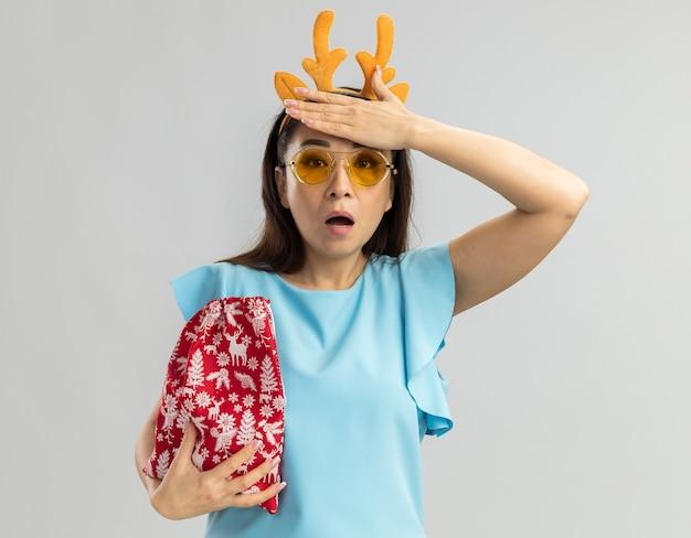 Junge frau in der blauen spitze, die lustigen rand mit hirschhörnern und gelben gläsern hält, die weihnachtliche rote tasche halten, die mit hand auf ihrem kopf verwirrt schaut
