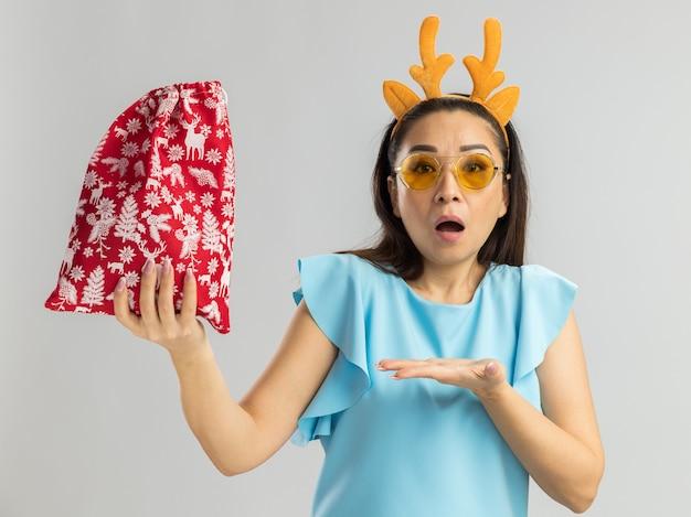 Junge frau in der blauen spitze, die lustigen rand mit hirschhörnern und gelben gläsern hält, die weihnachtliche rote tasche halten, die überrascht sieht, sie mit arm der hand darstellend