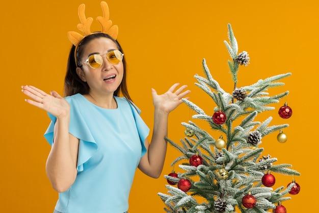 Junge frau in der blauen spitze, die lustigen rand mit hirschhörnern und gelben gläsern trägt, die kamera glücklich und aufgeregt stehen, die neben einem weihnachtsbaum über orange hintergrund stehen