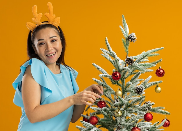 Junge frau in der blauen spitze, die lustigen rand mit hirschhörnern verziert, die weihnachtsbaum glücklich und positiv lächelnd fröhlich stehend über orange hintergrund verzieren