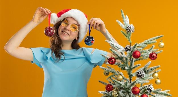 Junge frau in der blauen spitze und in der weihnachtsmannmütze, die gelbe brille hält, die weihnachtskugeln hält, die kamera glücklich und fröhlich stehen, steht neben einem weihnachtsbaum über orange hintergrund