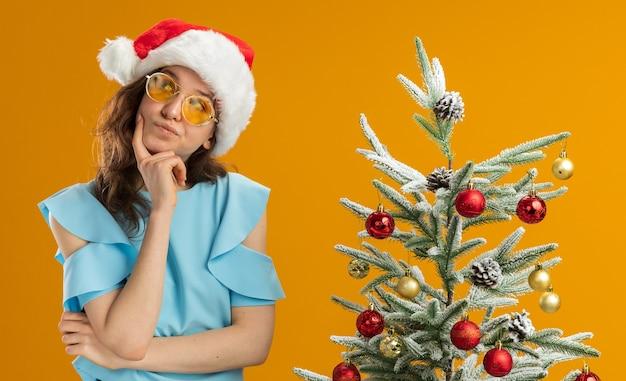 Junge frau in der blauen spitze und in der weihnachtsmannmütze, die gelbe brille trägt, die beiseite schaut verwirrt neben einem weihnachtsbaum über orange hintergrund steht