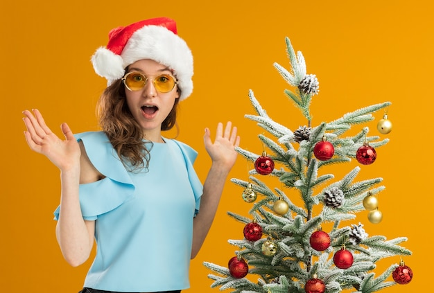 Junge frau in der blauen spitze und in der weihnachtsmannmütze, die gelbe brille trägt, die kamera betrachtet, überrascht und überrascht mit erhobenen armen, die neben einem weihnachtsbaum über orange hintergrund stehen