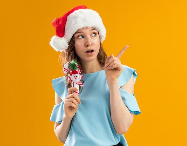 Junge frau in der blauen spitze und in der weihnachtsmannmütze, die weihnachtliche zuckerstange hält, die beiseite überrascht überrascht mit zeigefinger auf etwas zeigt