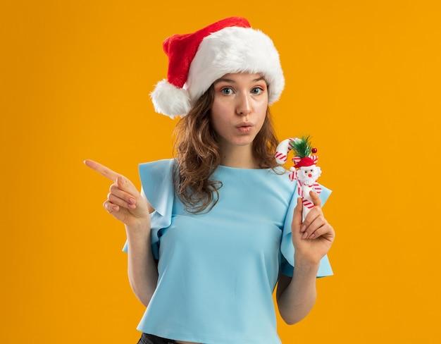 Junge frau in der blauen spitze und in der weihnachtsmannmütze, die weihnachtliche zuckerstange hält, die besorgt zeigt, mit zeigefinger zur seite zeigend