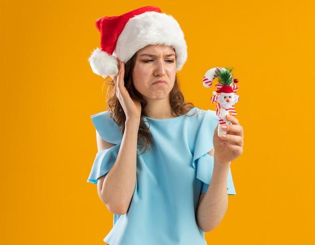 Junge frau in der blauen spitze und in der weihnachtsmannmütze, die weihnachtszuckerstange hält, die es verwirrt und unzufrieden betrachtet