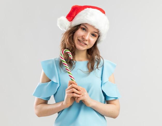 Junge frau in der blauen spitze und in der weihnachtsmannmütze, die zuckerstange hält, die fröhlich lächelnd schaut