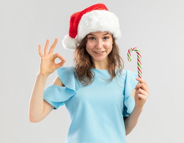 Junge frau in der blauen spitze und in der weihnachtsmannmütze, die zuckerstange hält, die glücklich und positiv schaut, ok zeichen zeigend