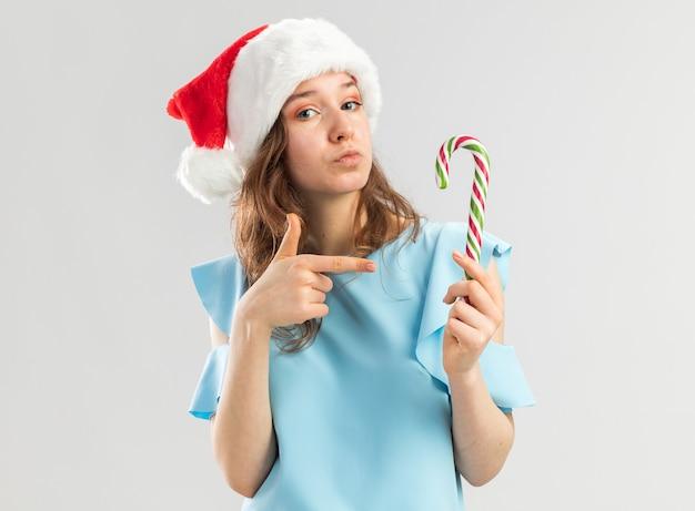 Junge frau in der blauen spitze und in der weihnachtsmannmütze, die zuckerstange hält, die mit zeigefinger darauf schaut und zuversichtlich schaut