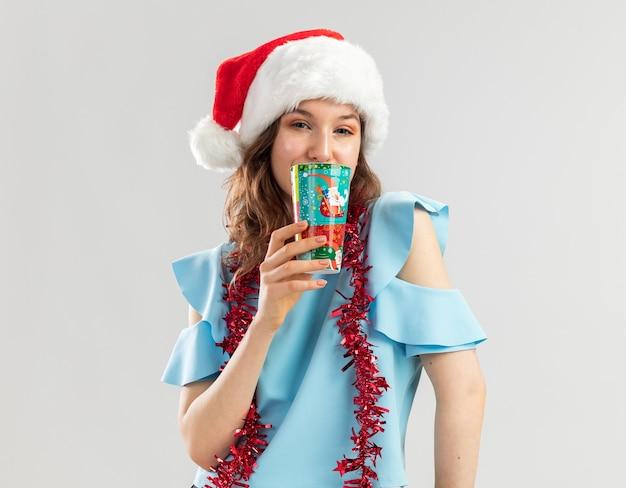 Junge frau in der blauen spitze und in der weihnachtsmannmütze mit lametta um ihren hals, der bunten pappbecher hält, der glücklich und positiv schaut