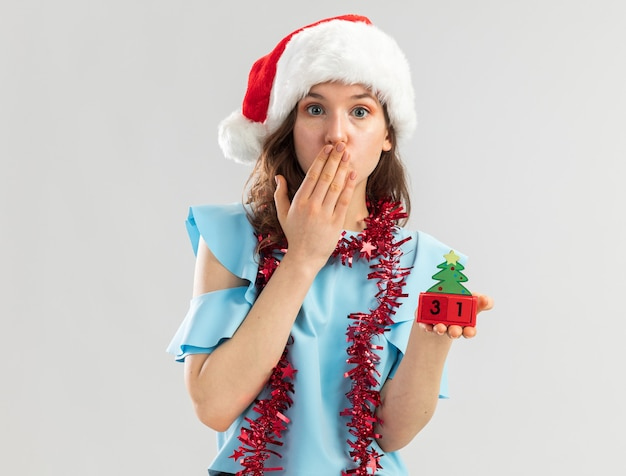 Junge frau in der blauen spitze und in der weihnachtsmannmütze mit lametta um ihren hals, der spielzeugwürfel mit glücklichem ney jahresdatum hält, das geschockt wird, mund mit hand bedeckend