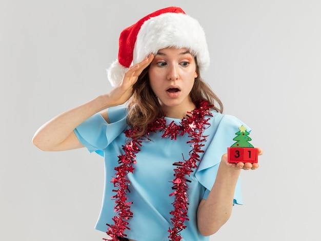 Junge frau in der blauen spitze und in der weihnachtsmannmütze mit lametta um ihren hals, der spielzeugwürfel mit glücklichem ney jahresdatum hält, das würfel erstaunt betrachtet