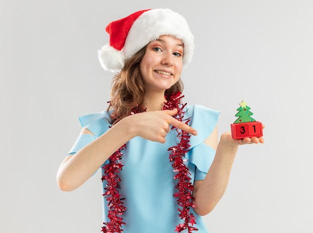 Junge frau in der blauen spitze und in der weihnachtsmannmütze mit lametta um ihren hals, der spielzeugwürfel mit neujahrsdatum hält, das mit zeigefinger auf würfel glücklich und fröhlich zeigt